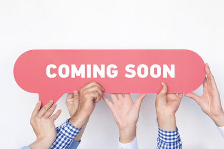 presently: Group of people holding the Coming Soon written speech bubble Stock Photo