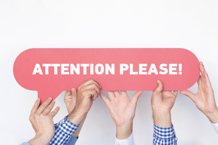 peril: Group of people holding the Attention Please written speech bubble Stock Photo