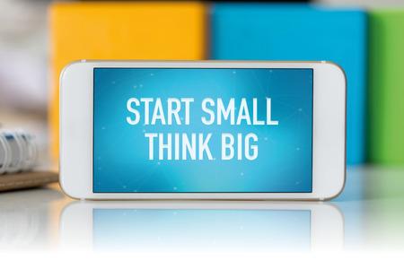 surpass: Smart phone which displaying Start Small Think Big Stock Photo