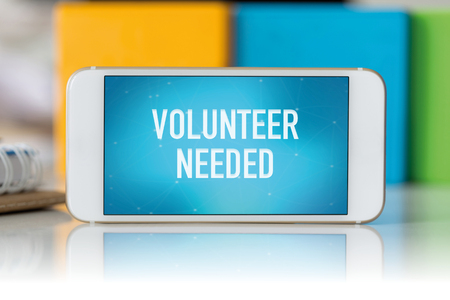 needed: Smart phone which displaying Volunteer Needed Stock Photo
