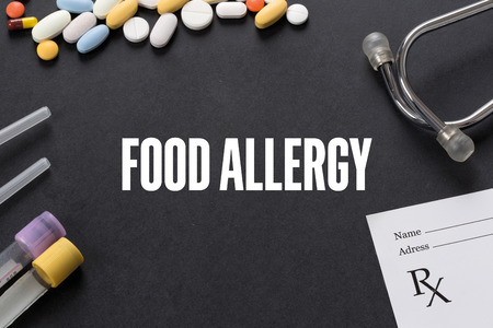 FOOD ALLERGY written on black background with medication Stock Photo