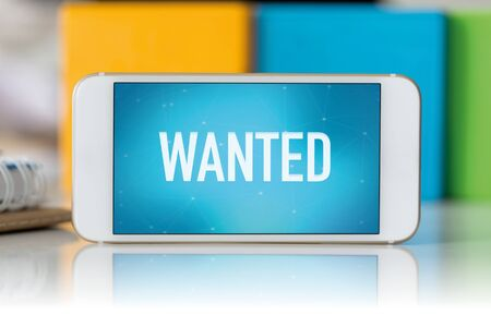recruit help: Smart phone which displaying Wanted Stock Photo