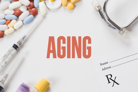 aging: AGING written on white background with medication Stock Photo