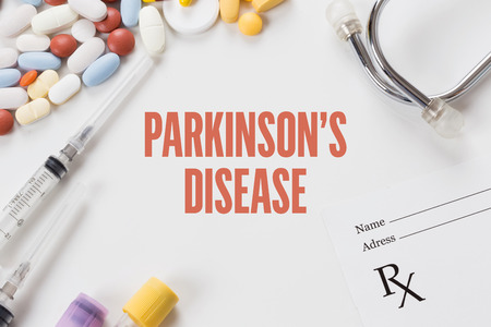 parkinson's disease: PARKINSONS DISEASE written on white background with medication Stock Photo