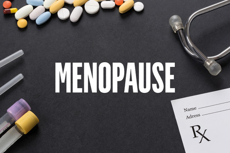 MENOPAUSE: MENOPAUSE written on black background with medication Stock Photo