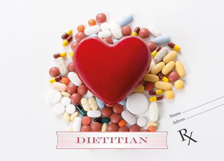 dietology: DIETITIAN written on heart and medication background