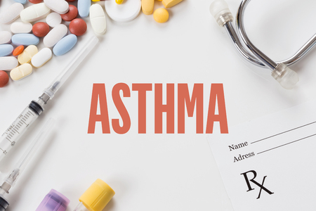 ASTHMA written on white background with medication Stock Photo
