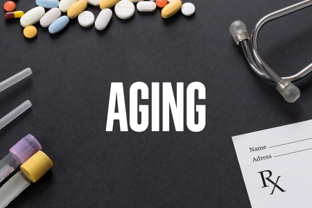 aging: AGING written on black background with medication Stock Photo