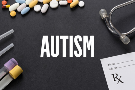 clinical psychology: AUTISM written on black background with medication Stock Photo