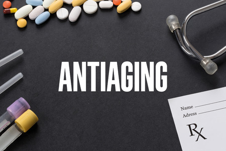 antiaging: ANTIAGING written on black background with medication