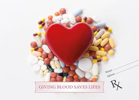 GIVING BLOOD SAVES LIFES written on heart and medication background