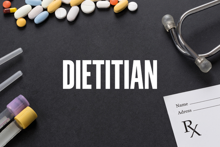 dietology: DIETITIAN written on black background with medication Stock Photo
