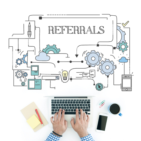 referrals: Man using laptop on workplace and REFERRALS concept Stock Photo