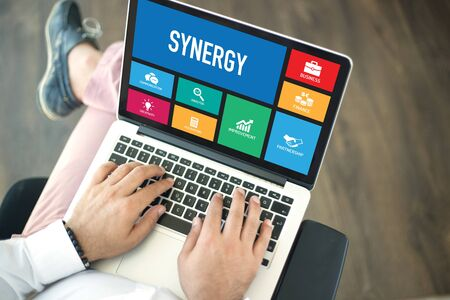 concurrence: People using laptop in an office and SYNERGY concept on screen Stock Photo