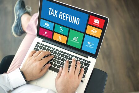 repayment: People using laptop in an office and TAX REFUND concept on screen Stock Photo