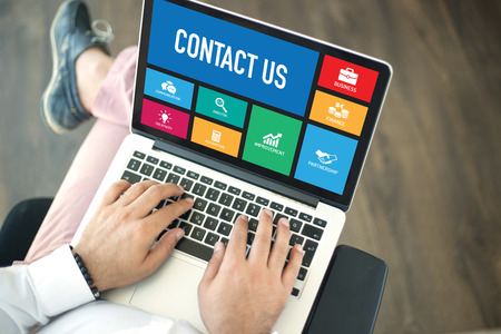 contactus: People using laptop in an office and CONTACT US concept on screen Stock Photo