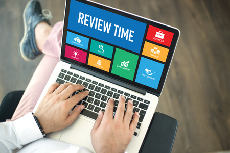 reassessment: People using laptop in an office and REVIEW TIME concept on screen