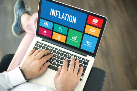 price uncertainty: People using laptop in an office and INFLATION concept on screen