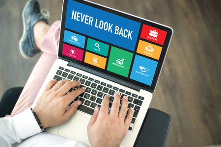 forthcoming: People using laptop in an office and NEVER LOOK BACK concept on screen