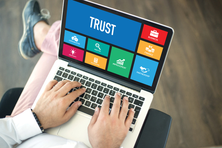 trust people: People using laptop in an office and TRUST concept on screen Stock Photo