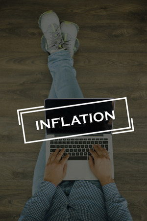 price uncertainty: Young man sitting on floor with laptop and INFLATION concept on screen