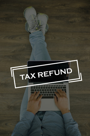 Young man sitting on floor with laptop and TAX REFUND concept on screen