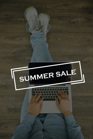 gift spending: Young man sitting on floor with laptop and SUMMER SALE concept on screen Stock Photo