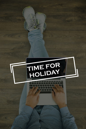 days off: Young man sitting on floor with laptop and TIME FOR HOLIDAY concept on screen Stock Photo