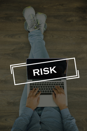 risky situation: Young man sitting on floor with laptop and RISK concept on screen