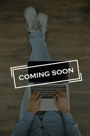 presently: Young man sitting on floor with laptop and COMING SOON concept on screen Stock Photo