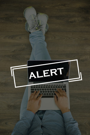 spy ware: Young man sitting on floor with laptop and ALERT concept on screen Stock Photo