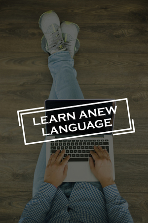 fluency: Young man sitting on floor with laptop and  LEARN A NEW LANGUAGE concept on screen