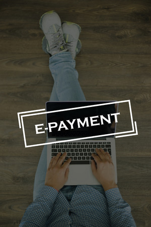 epayment: Young man sitting on floor with laptop and  E-PAYMENT concept on screen