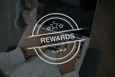 payoff: People Using Laptop and REWARDS Concept