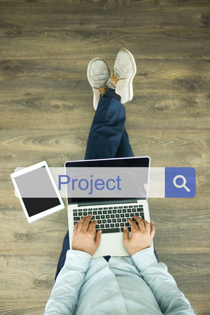 businessplan: Young man sitting on floor with laptop and searching PROJECT concept on screen Stock Photo