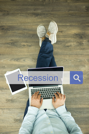 stagnation: Young man sitting on floor with laptop and searching RECESSION concept on screen