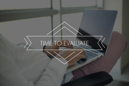 reevaluation: People Using Laptop and TIME TO EVALUATE Concept Stock Photo