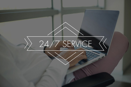 24x7: People Using Laptop and 247 SERVICE Concept Stock Photo