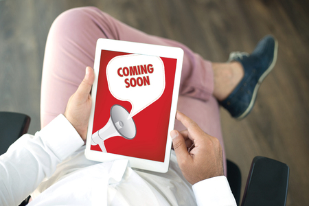 presently: People using tablet pc and COMING SOON announcement concept on screen Stock Photo