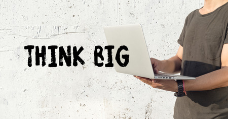 surpassing: Young man using laptop and THINK BIG concept on wall background Stock Photo