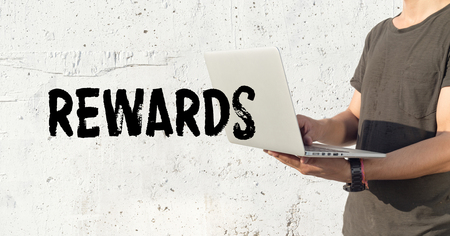 payoff: Young man using laptop and REWARDS concept on wall background