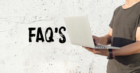 faq's: Young man using laptop and FAQS concept on wall background Stock Photo