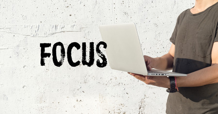 clear strategy: Young man using laptop and FOCUS concept on wall background Stock Photo