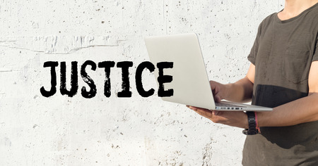 justness: Young man using laptop and JUSTICE concept on wall background