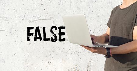 untrue: Young man using laptop and False concept on wall background Stock Photo