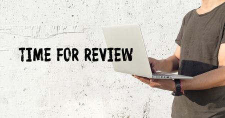 revision: Young man using laptop and TIME FOR REVIEW concept on wall background Stock Photo