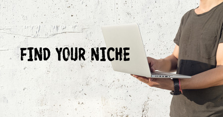 specialize: Young man using laptop and FIND YOUR NICHE concept on wall background