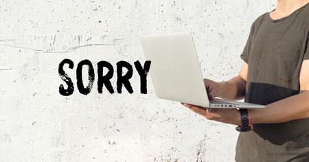 bad pardon: Young man using laptop and SORRY concept on wall background Stock Photo