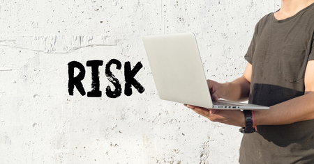 risky situation: Young man using laptop and RISK concept on wall background Stock Photo