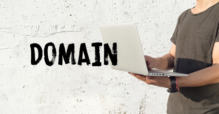edu: Young man using laptop and DOMAIN concept on wall background Stock Photo
